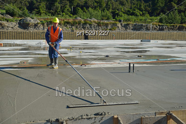 Builder Floating Off New Concrete For A Large Building Near Greymouth, South Stock Photo