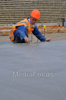 Builder Floating Wet Concrete In Foundations Of A Large Building Stock Photo