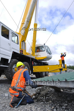 Builder Gives Directions To Crane Driver And Other Men Lifting The Roof Onto A New Dairy, Westland, New Zealand Stock Photo