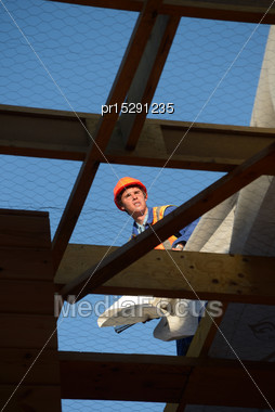 Builder Hammers Down Building Paper As The Team Puts The Roof On A Large Commercial Building Stock Photo