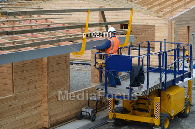 Builder Installs A Safety Guard Around The Roof Of A New Building Before The Iron Goes On Stock Photo