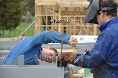 Builder Measures Cleats About To Be Welded On Steel Framing For Large Building Stock Photo