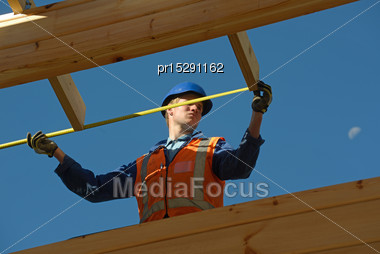 Builder Measures The Length Of The Wall Of A New Building Stock Photo