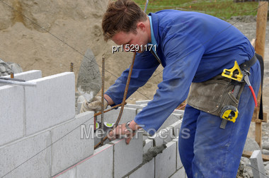 Builder Positions Blocks In Concrete Wall Stock Photo