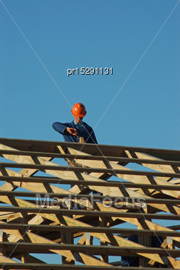 Builder Pulling Out A Nail While Working On The Roof Framing Stock Photo