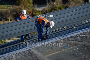 Builder Screws Down Roofing Iron For The Roof On A Large Commercial Building Near Greymouth, New Zealand Stock Photo
