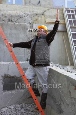 Builder Stood By Ladder Waving Stock Photo