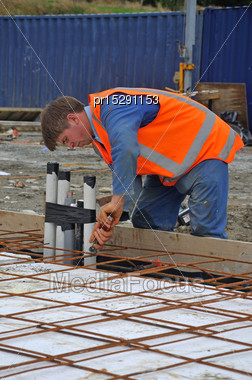 Builder Ties Off The Reinforcing Before Concrete Is Poured Into The Foundations Of A Large Building Stock Photo