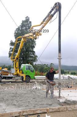 Builder Uses A Concrete Pump To Direct Wet Concrete Into The Foundations Of A Large Building Stock Photo