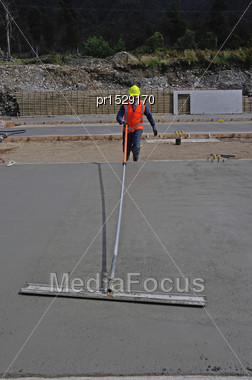 Builder Uses A Long Handled Trowel To Float Off A Wet Concrete Slab For A Large Building Stock Photo