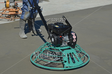 Builder Uses A Mechanical Float To Smooth New Concrete For A Large Building Stock Photo