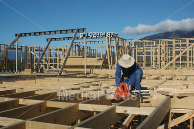 Builder Uses A Nail Gun On Flooring Job Stock Photo