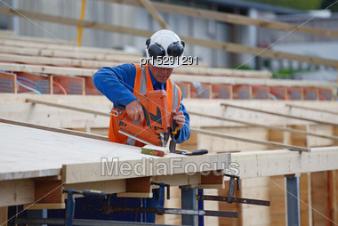 Builder Uses A Nail Gun To Secure Timber On The Verandah Of New Building Stock Photo