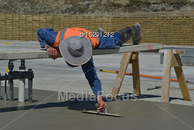 Builder Uses A Sawhorse And Plank To Position Himself While Floating Off New Concrete For A Large Building Near Greymouth, South Island, New Zealand Stock Photo