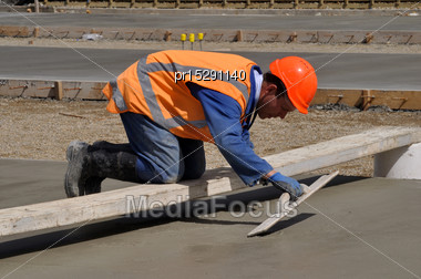 Builder Uses A Wooden Trowel To Float Off A Wet Concrete Slab For A Large Building Stock Photo