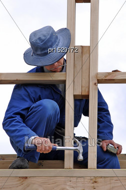 Builder Using Hammer To Nail Off Framework On Building Stock Photo