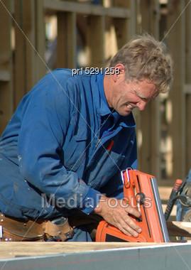 Builder Using Nail Gun On Building Site Stock Photo