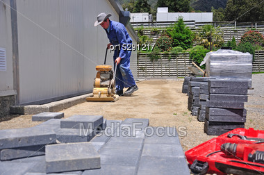 Builder Using A Vibrating Roller Before Setting Out Paving Stones For A Pathway At A Construction Site In Westland Stock Photo