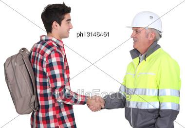 Builder Welcoming Apprentice Stock Photo
