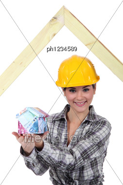 Builder With A House Made Of Money Stock Photo