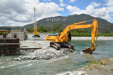 Builders Create A New Channel To Control The River While They Construct A Concrete Bridge Over A Small River In Westland, New Zealand Stock Photo