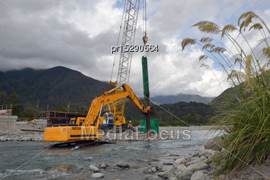 Builders Drive Pylons For A Concrete Bridge Over A River In Westland, New Zealand Stock Photo