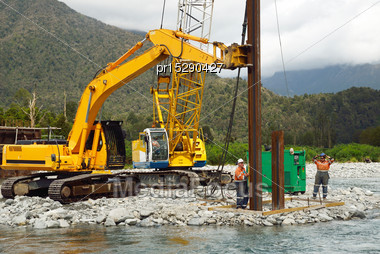 Builders Drive Pylons For A Concrete Bridge Over A Small River In Westland, New Zealand Stock Photo