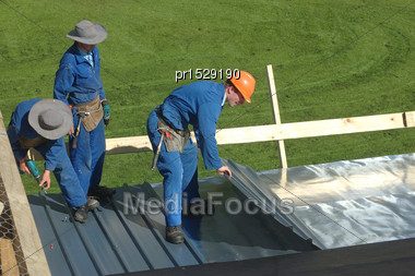 Builders Laying Out Roofing Iron On A Large House Stock Photo