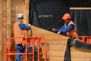 Builders Measure The Wall Of A Lockwood Style Building Stock Photo