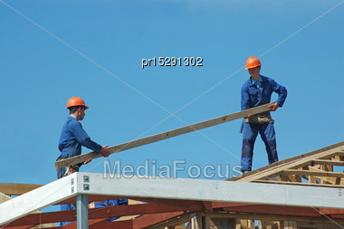 Builders Pass Along Timber For The Roof Of A Large House Stock Photo