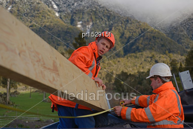 Builders Position A Large Purlin On The Roof Of A Building Stock Photo