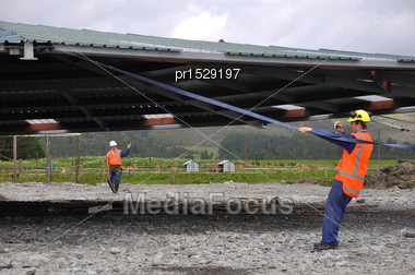 Builders Position The Roof As It Is Lifted Onto A New Dairy, Westland, New Zealand Stock Photo