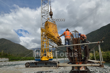 Builders Pour Concete Into The Pylon Of A Concrete Bridge Over A Small River In Westland, New Zealand Stock Photo