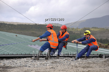 Builders Pull On The Line To Position The Roof For Lifting Onto A New Dairy, Westland, New Zealand Stock Photo