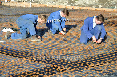 Builders Tie Off Sections Of Reinforcing For Concrete Slab Foundation Of A Large Building Stock Photo