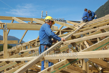 Builders Working On The Roof Of A Large House Stock Photo