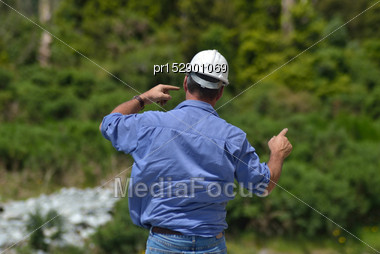 Building Foreman Instructs His Crane Driver While Constructing A Concrete Bridge Over A Small River In Westland, New Zealand Stock Photo