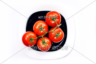 Bunch Of Five Tomato On Black And White Plates Stock Photo