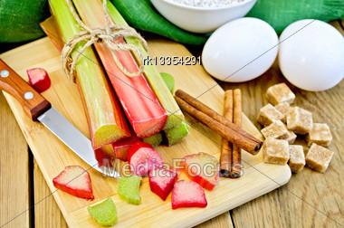 Bundle Of Stalks Rhubarb, Cut Pieces Of Rhubarb, Knife, Sugar Cubes, Cinnamon, Two Eggs, Flour, Napkin On Wooden Board Stock Photo