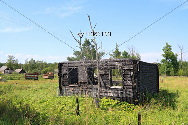 Burned Rural House On Green Field Stock Photo