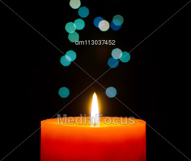 Burning Candle On A Christmas Lights Bokeh Background Stock Photo