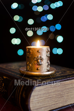 Burning Candle And Old Book On Bokeh Background Stock Photo