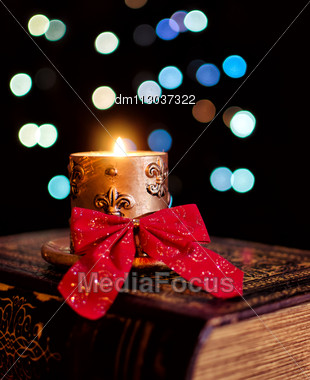 Burning Candle And Seasonal Decorations On Bokeh Lights Background Stock Photo