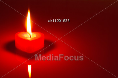 Burning Heart Shaped Candle Over Red Background Stock Photo