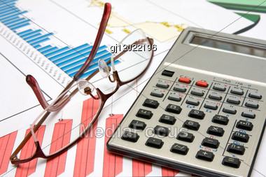 Business Balance. Calculator,glasses And Charts On The Desk Stock Photo