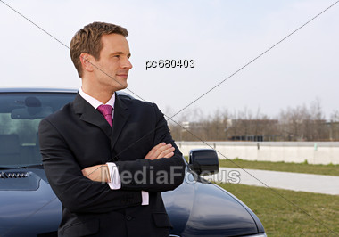 Business Man With Arms Crossed In Front Of Car Stock Photo
