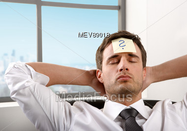 Business Man In Office, Thoughtful, Questionmark On The Forehead Stock Photo