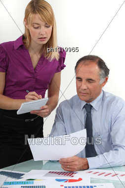Business People Looking At Statistics Stock Photo