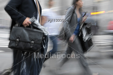 Business People Morning Rush Hour In Motion Blur, Man Carrying Clothing From Dry Cleaning Shop Stock Photo