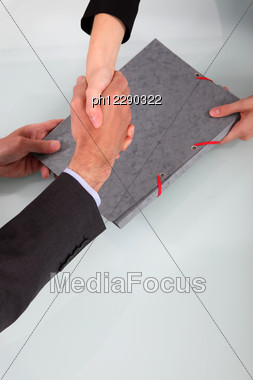 Business People Shaking Hands Over A Folder Stock Photo